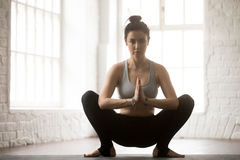 Young attractive woman in Malasana pose, white loft studio backg. Young attractive yogi woman practicing yoga concept, sitting in Malasana exercise, Garland pose Royalty Free Stock Photo
