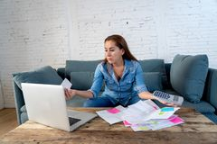 Young attractive woman managing paying bills and calculating finances felling stressed and worried royalty free stock image