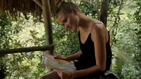 Young attractive woman with map of island enjoying in the jungle. stock video footage