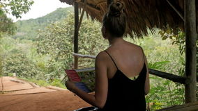 Young attractive woman with map of island enjoying in the jungle. stock footage