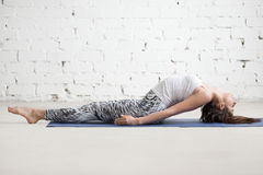 Young attractive woman in Matsyasana pose, white studio backgrou Stock Image