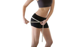 Young attractive woman measuring her hips with tape measure Stock Photo