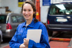 Young attractive woman mechanic working at the garage Stock Images