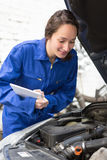 Young attractive woman mechanic working at the garage Stock Photos