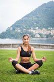 Young attractive woman meditating on the grass outdoors. Near the lake Royalty Free Stock Images