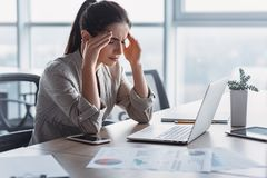 Young attractive woman at modern office desk. She has severe headache. Office syndrome concept royalty free stock photo