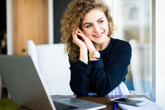 Young attractive woman at a modern office desk, working with laptop, looking at the window, thinking about a post. Stock Image