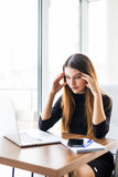 Young attractive woman at modern office desk, working on laptop, massaging temples to forget about constant headaches.  Stock Image