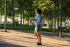 Young and attractive woman with morning coffee standing in the park. Stock Photography