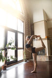 Young attractive woman in Natarajasana pose, home interior backg Royalty Free Stock Images