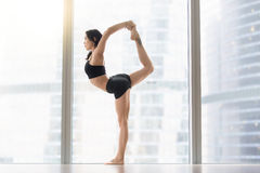 Young attractive woman in Natarajasana pose near the floor windo. Young attractive woman practicing yoga, standing in Natarajasana exercise, Lord of the Dance Royalty Free Stock Photos