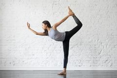 Young attractive woman in Natarajasana pose, studio background. Young attractive woman practicing yoga, stretching in Natarajasana exercise, Lord of the Dance Royalty Free Stock Image