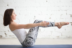 Young attractive woman in navasana pose, white studio background Royalty Free Stock Photo