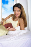 Young attractive woman in nightgown lying relaxed on bed reading Stock Photo