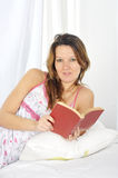 Young attractive woman in nightgown lying relaxed on bed reading novel book Stock Photo