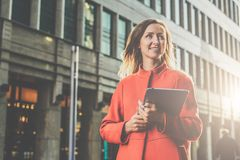 Young attractive woman in orange coat walks down city street holding tablet computer. Girl student going to lecture Royalty Free Stock Photo