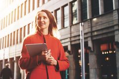 Young attractive woman in orange coat walks down city street holding tablet computer. Girl student going to lecture Royalty Free Stock Photos