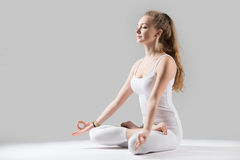 Young attractive woman in Padmasana pose with mudra, grey studio. Young attractive woman practicing yoga, sitting in Padmasana exercise, Lotus pose on meditation stock photography
