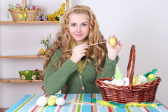 Young attractive woman painting easter eggs Royalty Free Stock Images