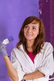 Young attractive woman paints white wall with purple paint brush. Young attractive woman paints white wall and purple paint brush Royalty Free Stock Photo