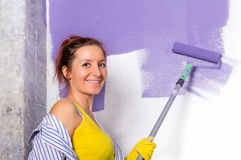 Young attractive woman paints white wall with purple paint rolle. Young attractive woman paints white wall and purple paint roller Stock Photos
