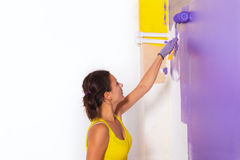 Young attractive woman paints white wall with purple paint rolle Stock Image