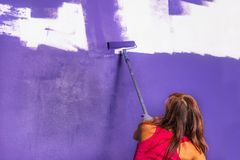 Young attractive woman paints white wall with purple paint rolle. Young attractive woman paints white wall and purple paint roller Royalty Free Stock Photos