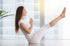 Young attractive woman in Paripurna Navasana pose against floor. Young attractive happy woman practicing yoga, sitting in balance exercise, Paripurna Navasana Royalty Free Stock Image