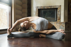 Young attractive woman in Parivrtta Janu Sirsasana pose, home in Stock Photos
