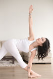Young attractive woman in Parivrtta Trikonasana pose, the living Royalty Free Stock Images
