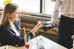 Young attractive woman paying in cafe with contactless smartphone payment royalty free stock photography