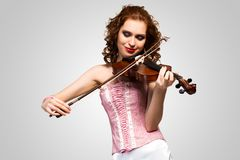 Young attractive woman in pink corset on a violin. Closed her eyes and smiles stock image