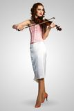 Young attractive woman in pink corset on a violin. Young attractive woman in pink corset playing the violin, enjoys music royalty free stock photo