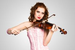 Young attractive woman in pink corset on a violin. Young attractive woman in pink corset playing the violin, enjoys music stock image