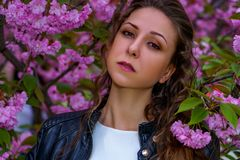 Young attractive woman in pink flowers in the garden. Girl with curly hair in white dress and black leather jacket outdoor
