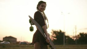Young attractive woman in plaid shirt, shorts and tank top holding longboard and looking in the camera during the sunset stock video footage