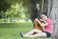 Young attractive woman playing acoustic guitar Royalty Free Stock Images