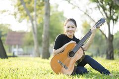 Young attractive woman playing acoustic guitar Stock Images