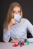 Young attractive woman playing poker over grey Stock Photography