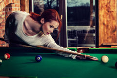 Young attractive woman plays the game of snooker pool table. Fun and competition concept Royalty Free Stock Photos