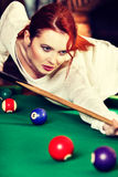Young attractive woman plays the game of snooker pool table. Fun and competition concept Stock Photo