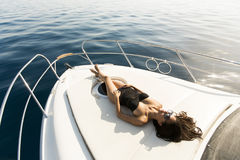 Young attractive woman poses on luxury yacht floating on sea stock photos