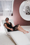 Young attractive Woman posing on couch. Young attractive Woman with sunglasses posing on couch Stock Photography