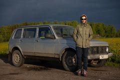 Young attractive woman posing outdoors with her SUV on an empty dirt road against the background of the field royalty free stock image