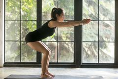 Young attractive woman in Utkatasana pose, studio background. Young attractive woman practicing fitness against big window, doing squat exercise, warming up Stock Image