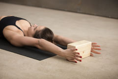 Young attractive woman practicing iyengar yoga using wooden bloc. Young attractive yogi woman practicing iyengar yoga using wooden block, lying on the floor Stock Photography