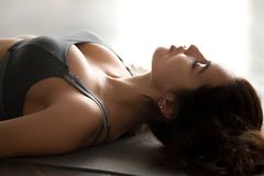 Young attractive woman practicing yoga, Dead Body pose, close up stock images