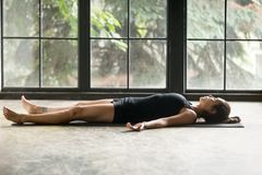 Young attractive woman in Corpse pose, studio background. Young attractive woman practicing yoga at home, lying in Savasana exercise, Corpse pose, working out stock photo