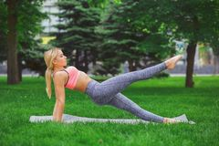 Young attractive woman practicing yoga outdoors Royalty Free Stock Image