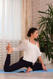 Young attractive woman practicing yoga, sitting in Mermaid exercise, Eka Pada Rajakapotasana pose, working out, wearing white shir Stock Photography